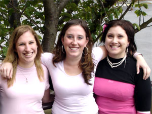 Group of three young women standing with their arms around each other