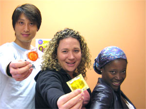 two females and a male holding a yellow condom