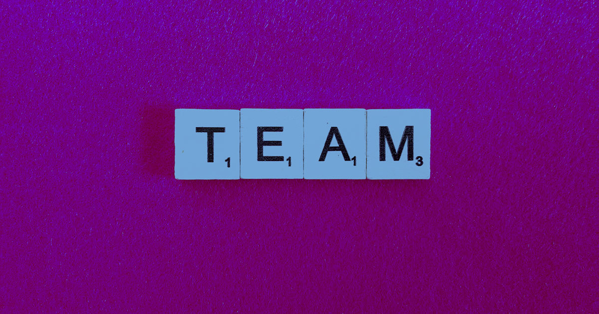 "Four crossword puzzle pieces laid out say, ""TEAM""."
