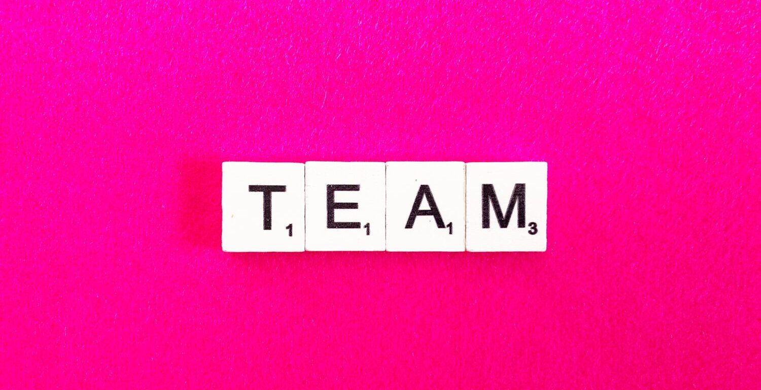 """Four crossword puzzle pieces laid out say, """"TEAM""""."""