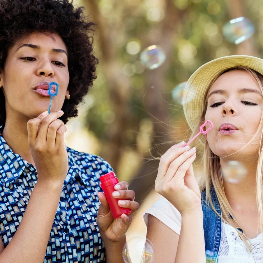 Two people stand in a sunny park blowing bubbles that are floating in air.