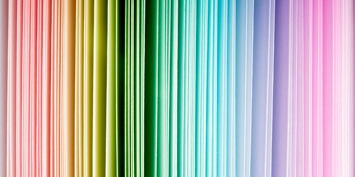 Photograph of book pages that range from left to right in shades of the rainbow: red through pink