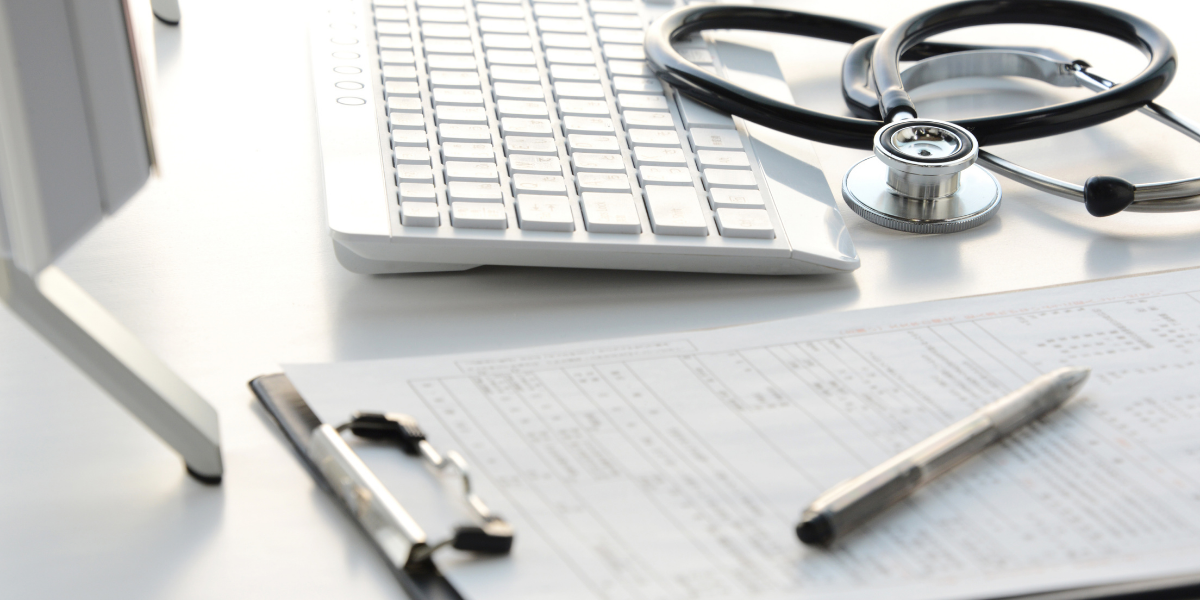 Photograph of computer keyboard, clipboard, pen and stethoscope on a desk.